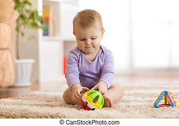 Cute baby playing with colorful toys sitting on carpet in white sunny bedroom. Child with educational toy. Early development.