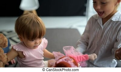 Cute baby playing with elder sister and caring father