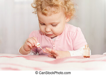 Cute baby playing with mothers manicure cosmetics
