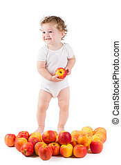 Cute baby playing with red apples, standing