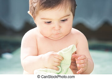Cute baby playing with towel