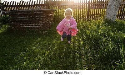 Cute baby running on the garden.