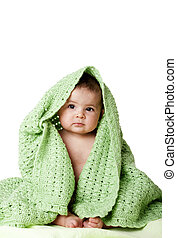 Cute baby sitting between green blanket.