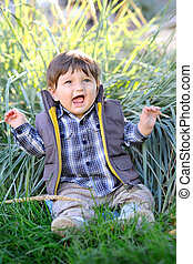 cute baby sitting in the grass outdoors in autumn jacket