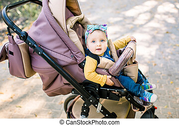 cute baby sitting on baby stroller carriage and posing smiling