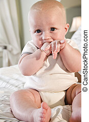 Cute baby sitting on bed with hand in mouth