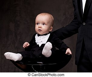 Cute baby sitting on chair.