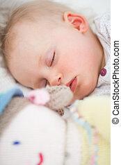 Cute baby sleeping next to her stuffed teddy bear