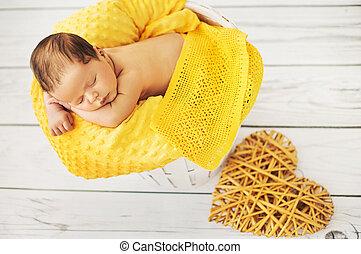 Cute baby sleeping on a yellow blanket