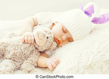 Cute baby sleeping with teddy bear toy on a white soft bed at home