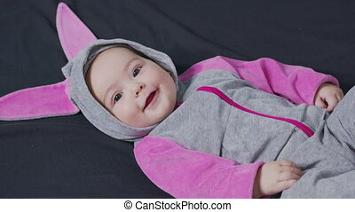 Cute baby smiling and looking in the camera close up. Little kid in bunny costume, top view