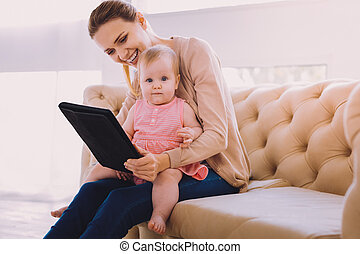 Cute baby smiling while a babysitter showing her lovely pictures