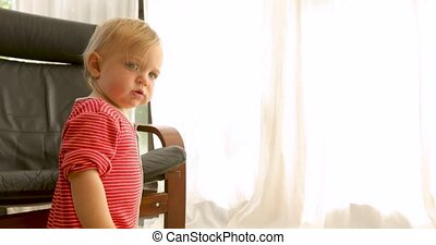 Cute baby standing by armchair - Side view of adorable blond...