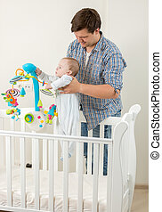 Cute baby standing in cot and playing with carousel with his father