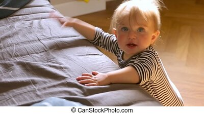 Cute baby standing leaning on bed - From above adorable kid...