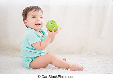 cute baby take green apple