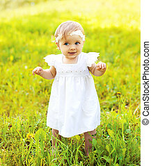 Cute baby walking on the grass in sunny summer day
