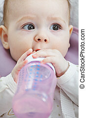 Cute baby with a bottle closeup