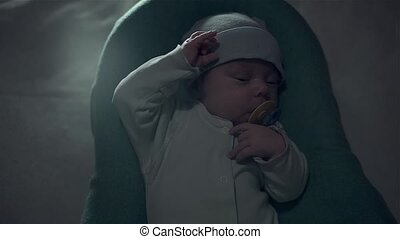 Cute baby with a pacifier in his mouth lying in a cot.