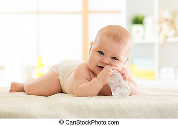 Cute baby with bottle on bed