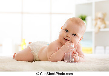 Cute baby with feeding bottle on bed
