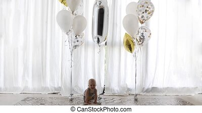 Cute baby with festive balloons