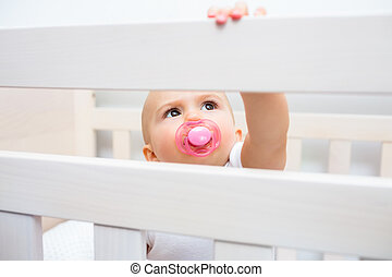 Cute baby with pacifier in mouth in