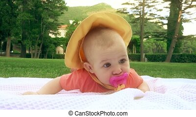 Cute baby with pink pacifier laying on the towel on the...