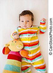 Cute baby with Striped colored pajamas and a cat toy lying on bed