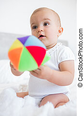Cute baby with toy sitting on bed