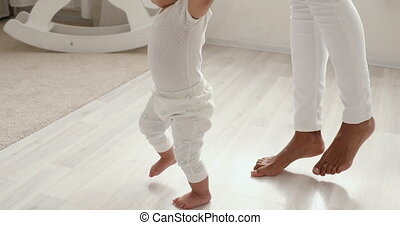Cute barefoot african baby girl learning to walk with mom