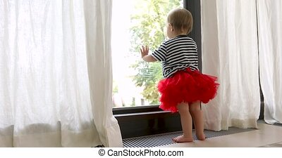 Cute barefoot baby girl in red skirt looking at window -...