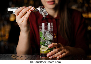 cute barmaid in a red dress prepares a mojito using ice tongs