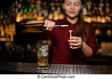 cute barmaid prepares a mojito in a crystal glass, adding dark rum