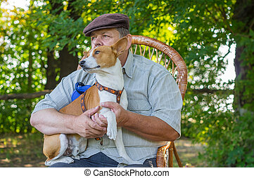 Cute basenji dog sitting on the hands of it's  senior master while resting in summer park