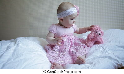 Cute beautiful baby girl sitting on a bed in pink dress