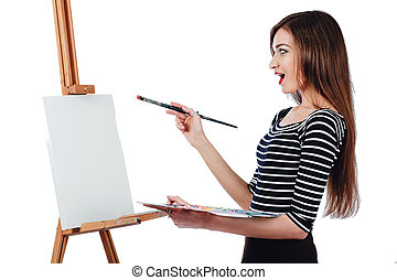 Cute beautiful girl artist painting a picture on  canvas  easel. Space for text. Studio white background, isolated.