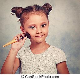 Cute beautiful small kid girl applying tonal cosmetic on the...