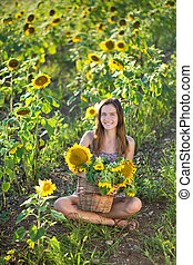 Cute beautiful young girl lady woman sitting on a field with...