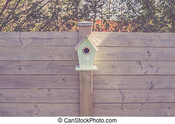 Cute birdhouse on a wooden fence