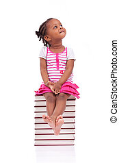 Cute black african american little girl seated in a stack of books, isolated on white background - African people - Children