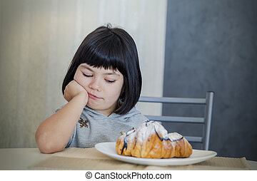 Cute black hair little girl looking at croissant