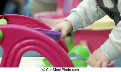 Cute blond babe is playing with toys in the mall. Children's area to leave children when shopping