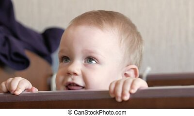 Cute blond babe shows playing in a baby crib with a bolt. He smiles and twists it in his arms