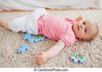 Cute blond baby playing with puzzle pieces while lying on a carpet in the living room