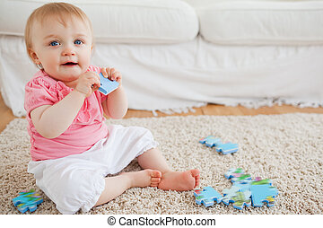Cute blond baby playing with puzzle pieces while sitting on a carpet in the living room