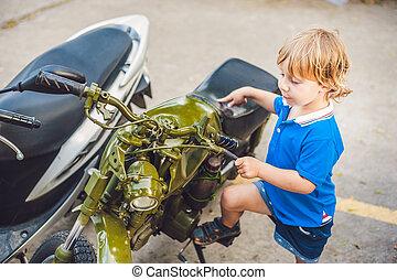 Cute blond boy looking at vintage motorcycle eatables new motorbike