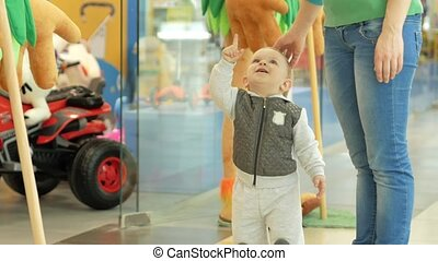 Cute blond boy of two years shows mom big soft toys in the mall at the store entrance