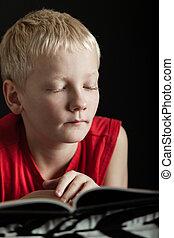 Cute blond boy reading book