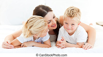 Cute blond boy with his sister and his mother lying on a bed